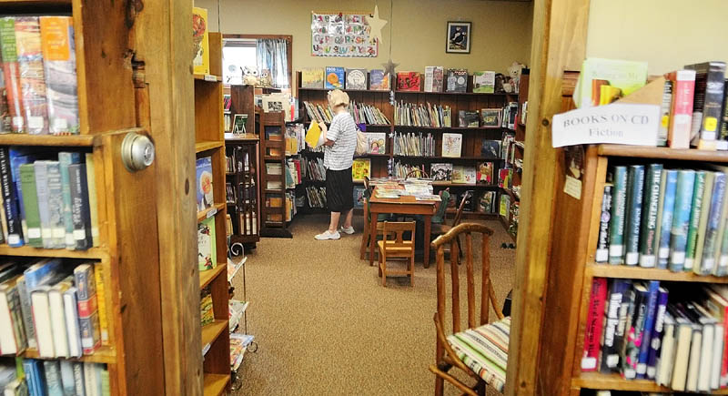 Linda Gardner looks for a book for her niece in the children's room on Saturday morning at the South China Public Library.