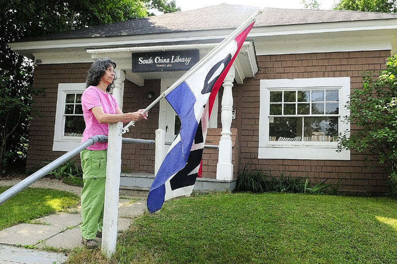 Volunteer Linda Gray puts out the open flag on Saturday morning at the South China Public Library.