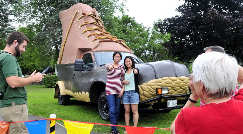 """Regina Oliver photographs visiting students Amanda Xiao, left, and Mona Wang in front of the L.L. Bean Bootmobile at Gifford's Ice Cream in Waterville on Sunday as part of the Freeport company's 100th anniversary. Oliver and husband Herb are hosting the students and said, """"We wanted to show them an iconic Maine company like L.L. Bean today."""" Eric Smith, left, drove the vehicle."""