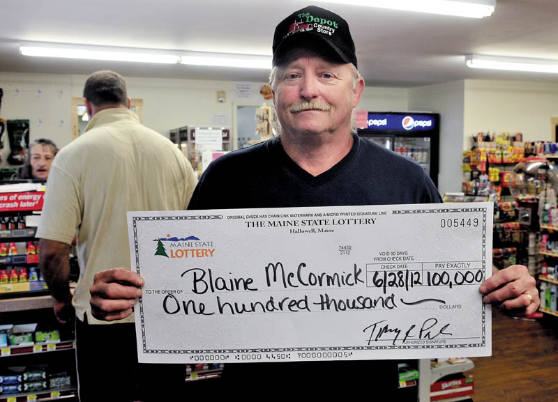 Blaine McCormick of Unity on Monday holds a mock check for the $100,000 he won from a state lottery ticket he purchased at the Depot Store in Unity where he works.