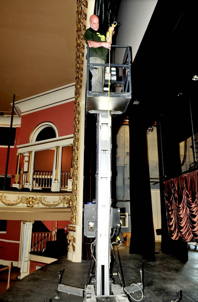 Mike Martineau takes measurements before hanging a stage curtain at the Waterville opera House on Thursday for the Maine International Film Festival.