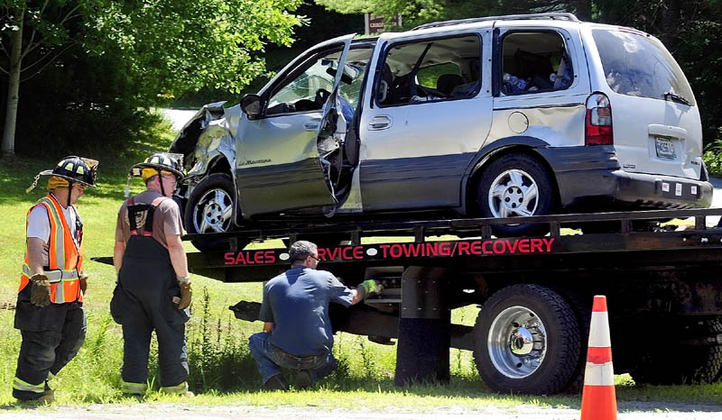 Firefighters talk to a tow truck operator as he loads up a van involved in a two-vehicle crash at the corner of U.S. Route 202 and Bog Road this afternoon in Monmouth.