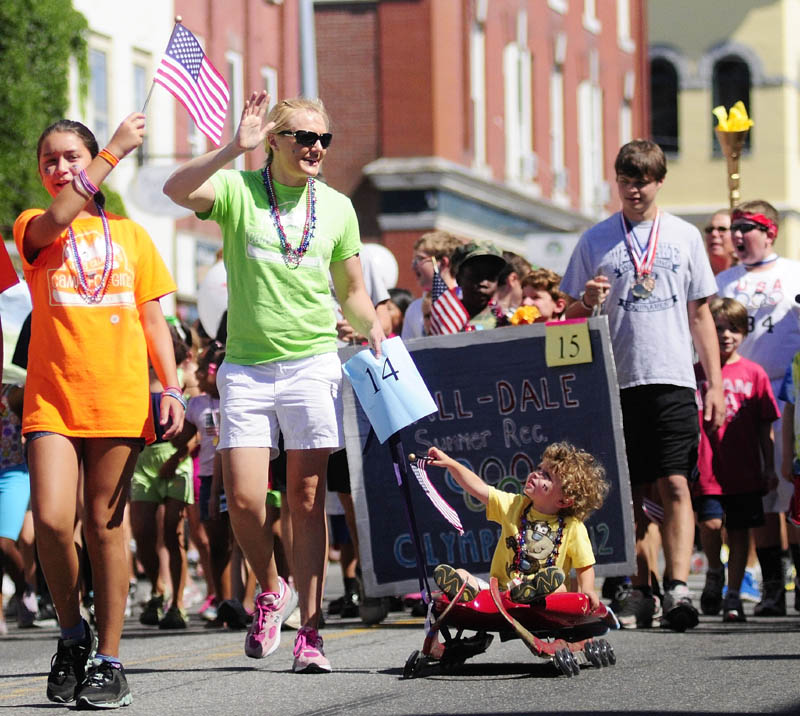 Olympic luger Julia Clukey, center, pulls Lucas Waterhouse 31⁄2, on a roller luge sled during the Old Hallowell Day parade along Water Street on Saturday morning.