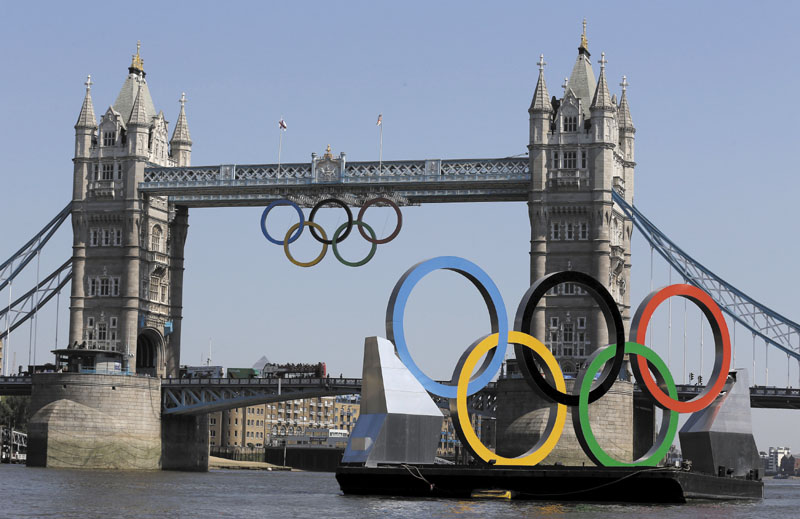 THE GAMES ARE HERE: Olympic Rings hang from the Tower Bridge beyond a set of rings floating on the River Thames on Thursday in London. The city will host the 2012 London Olympics with opening ceremonies scheduled for tonight. 2012 London Olympic Games;Summe