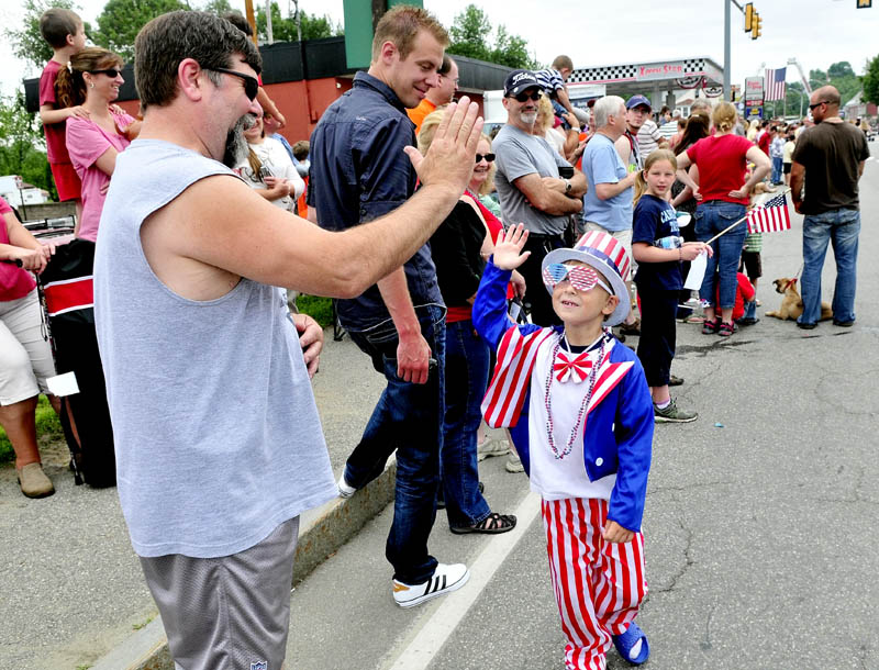 HIGH FIVE ON THE FOURTH: Dressed as Uncle Sam, Zachary Wentworth high-fives David Fuller during the Winslow Family 4th of July parade on Wednesday. Bay Street was packed with parade watchers.