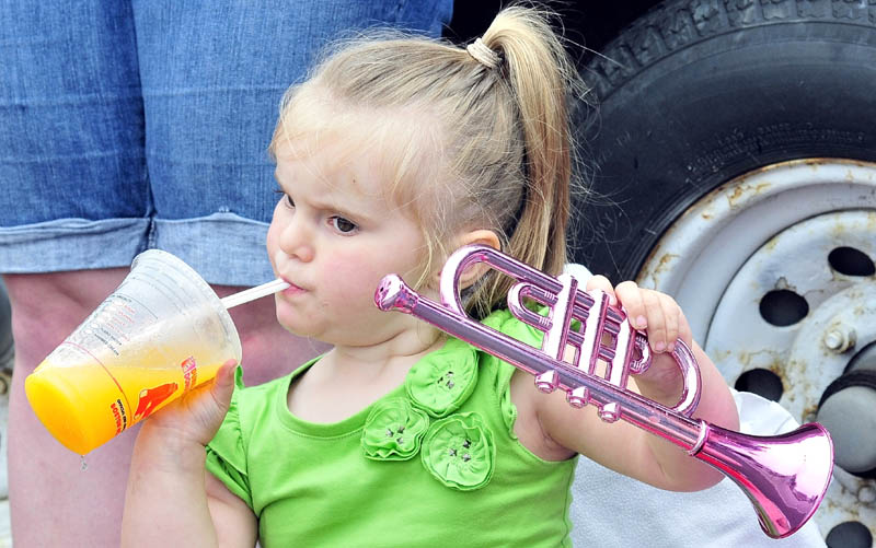 HOT PARADE: Hailee Penney takes a drink to cool off between playing a toy horn and watching the Winslow Family 4th of July parade on Wednesday.