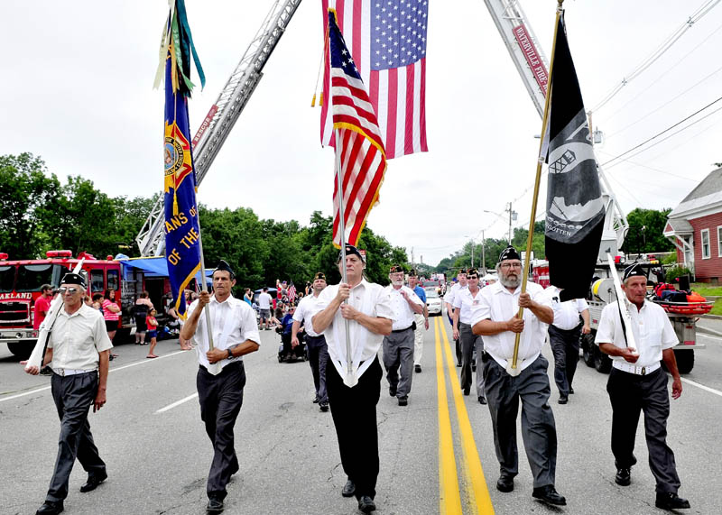 PATRIOTIC FORM: A Veterans of Foreign Wars color guard marches under an American flag during the 22nd annual Winslow Family 4th of July parade in Winslow on Wednesday. Hundreds watched the two-hour parade of floats.