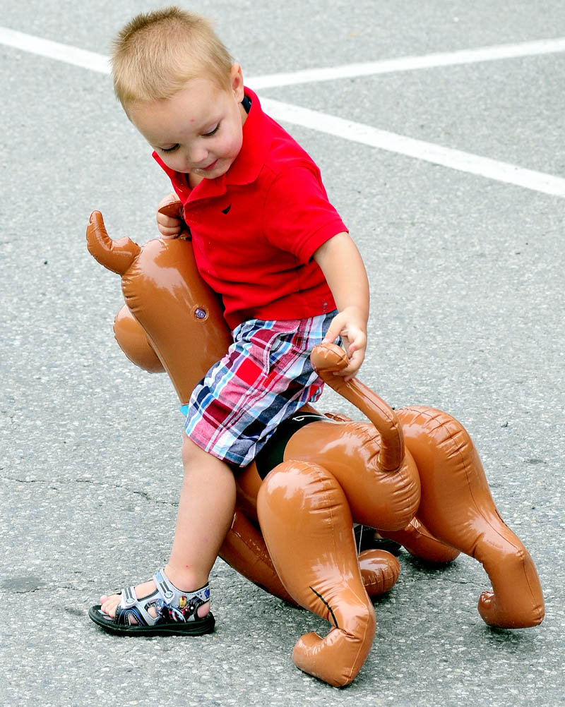 BY THE TAIL: Aiden Troxell grabs the tail of his blow-up dog while waiting for the Winslow Family 4th of July parade to start on Wednesday.