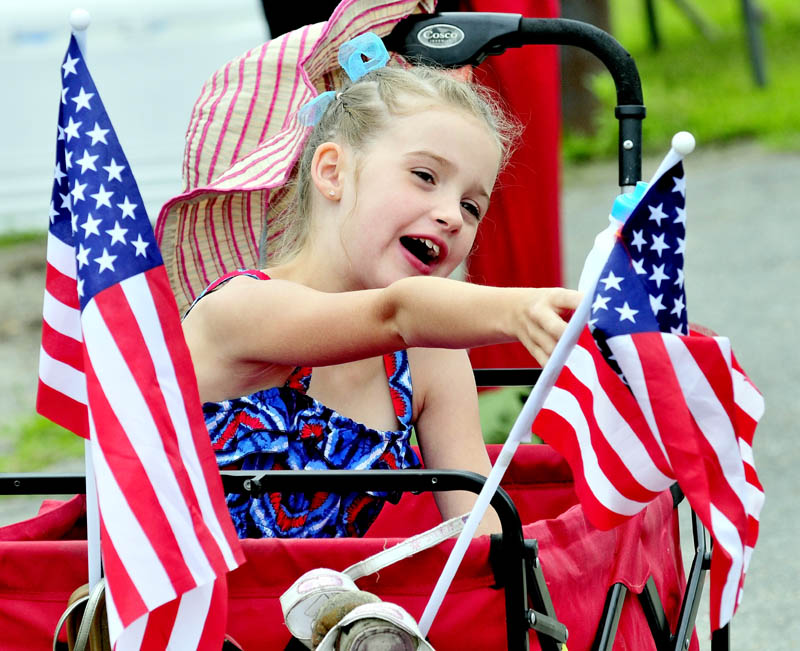 YOUNG PATRIOT: Between two American flags, Alexys Rolfe reacts as units go by in the Winslow Family 4th of July parade on Wednesday.