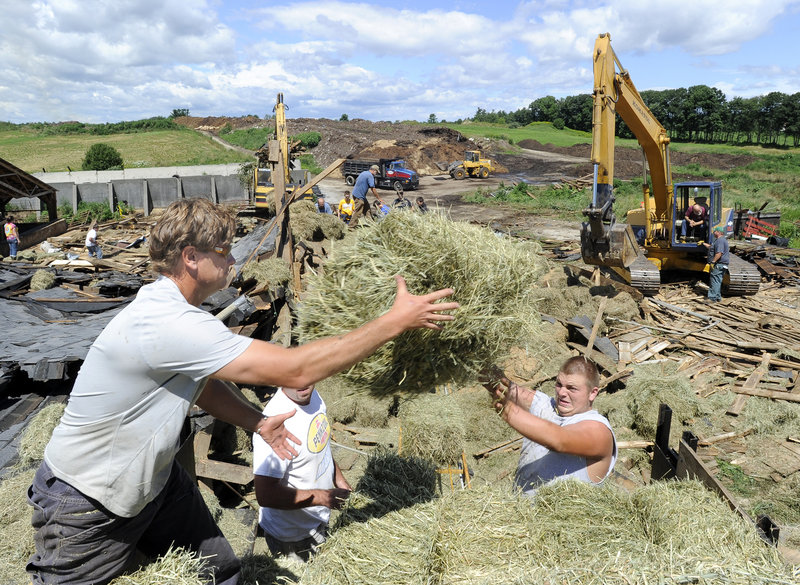 In this July 2010 file photo, Art McNeally, Jason Mitsin and Nate Faulkner load hay onto a truck at Benson dairy farm in Gorham. A novel program intended to raise money for financially strapped New England dairy farmers and educate consumers about the benefits of local farms is reorganizing after it had to pay more than $60,000 in back taxes.