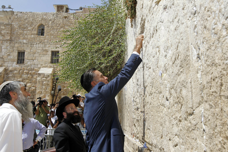 Republican presidential candidate and former Massachusetts Gov. Mitt Romney places a prayer note as he visits the Western Wall in Jerusalem on Sunday.