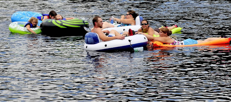 DRIFTING AWAY: These people on tubes and rafts were among the dozens who floated down the Kennebec River below the Solon/Embden bridge to cool off on Sunday.