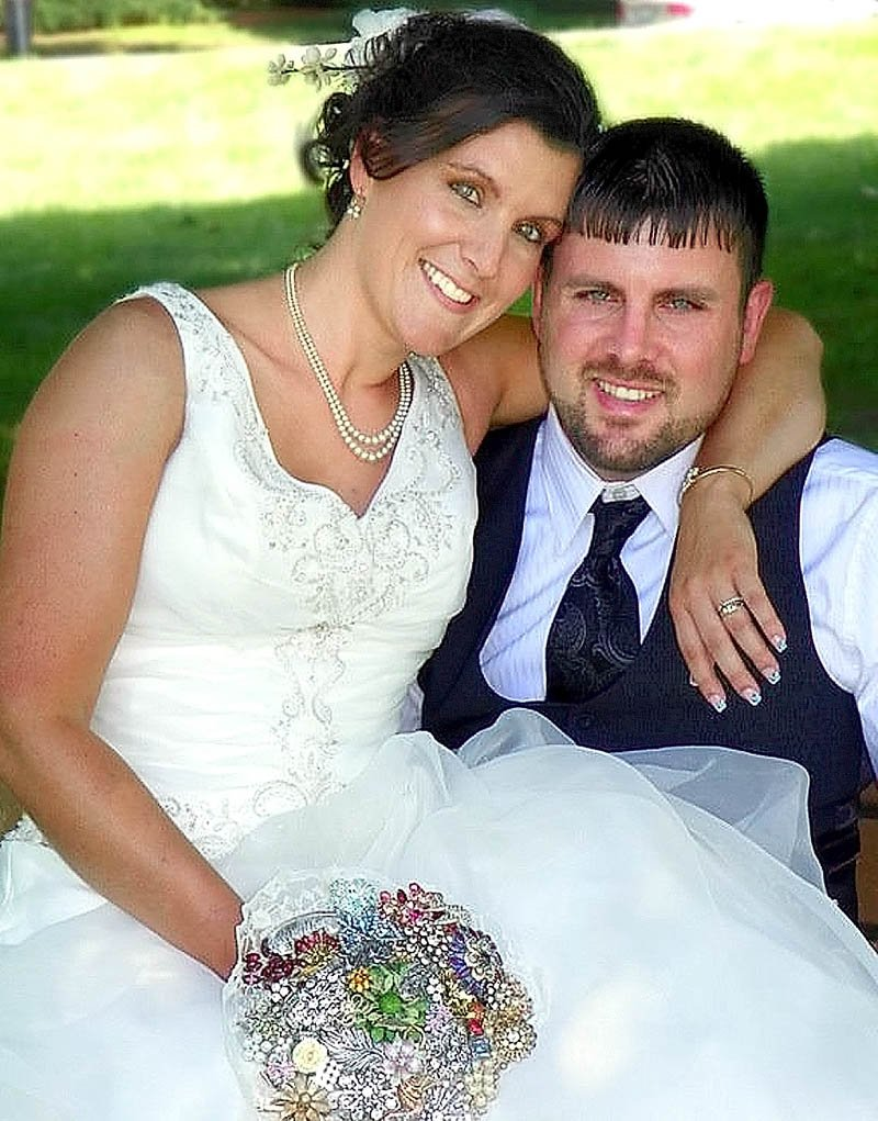 LOST TREASURE: Sara and Josh Norton were married June 30 at the park beside the Winslow Town Office. Here, Sara Norton is holding a bouquet made of family brooches that went missing after the wedding.