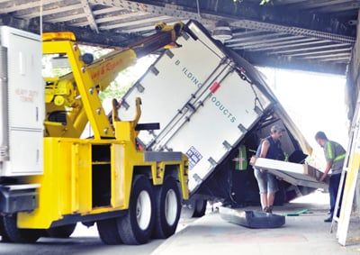 Staff photo by Joe Phelan KDT Towing workers remove doors from a box truck stuck under the railroad trestle Thursday morning on Water Street in downtown Augusta.