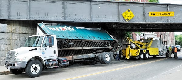 Staff photo by Joe Phelan KDT Towing workers remove a box truck stuck under the railroad trestle Thursday morning on Water Street in downtown Augusta.