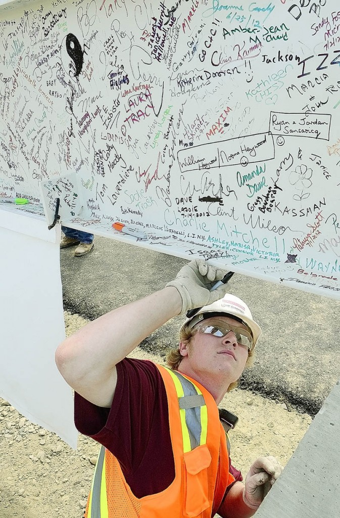 Staff photo by Joe Phelan Construction worker Tyler Bartlett autographs the final beam before it gets lifted into place before topping out ceremony on Monday morning at the construction site of Maine General Medical Center's new regional hospital in north Augusta.