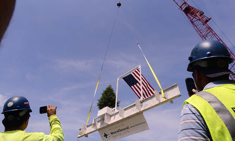 Staff photo by Joe Phelan Workers record the final beam being lifted into place during the topping out ceremony on Monday morning at the construction site of Maine General Medical Center's new regional hospital in north Augusta. The beam was signed by many people and the tree was dug up from and will be returned to the site.
