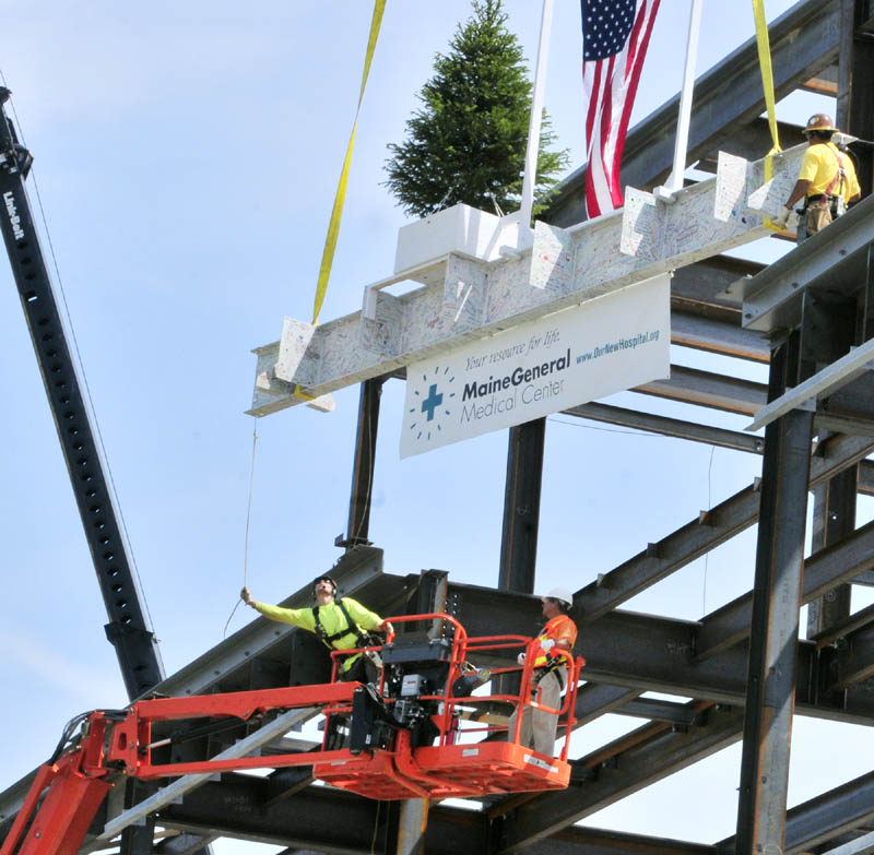 John Milbrand, construction manager for MaineGeneral Medical Center's new regional hospital, on right in lift, puts in the bolts on the final beam during the topping-out ceremony Monday morning at the construction site in north Augusta. The beam was signed by many people, and the tree was dug up from and will be returned to the site.