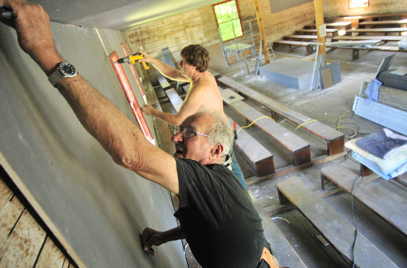 Earle Welch, left, and Don Laliberte, of Mount Vernon, owner of Don Laliberte Dry Wall, hangs drywall on Friday at the Wayne Town House.