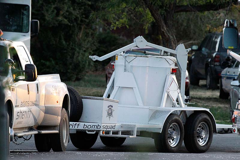 "A bomb disposal vehicle arrives near the apartment of alleged gunman James Holmes today in Aurora , Colo. Authorities reported that 12 died and more than three dozen people were shot during an assault at a movie theatre midnight premiere of ""The Dark Knight Rises"" early Friday."