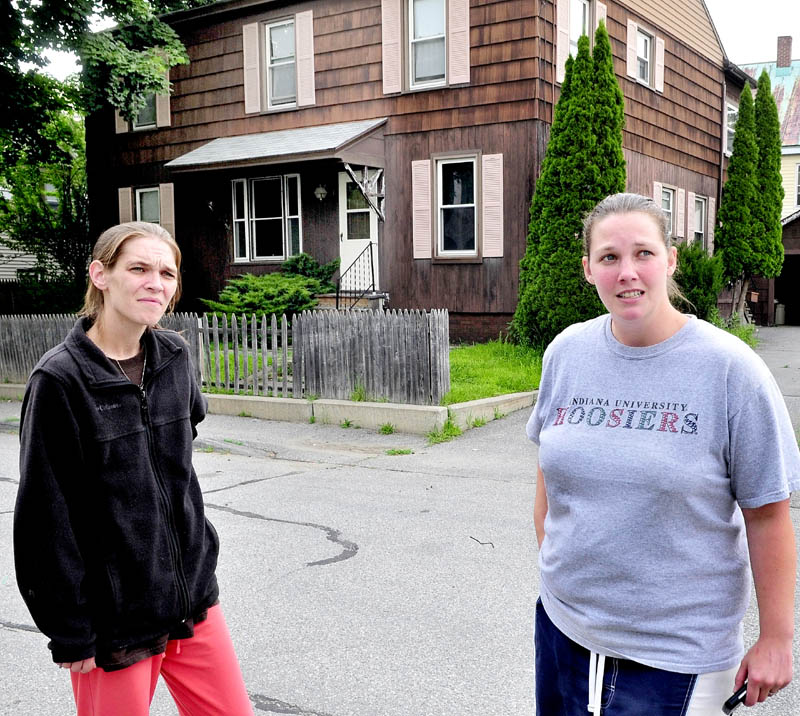 NEIGHBORS: Neighbors Jessica Veilleux, left, and Cassie Sirois speak in front of the apartment house where their neighbor Matt Savinelli was taken into custody by police Wednesday morning following a standoff.