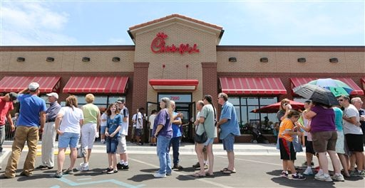 """Customers stand in line for a Chick-fil-a meal at the chain's restaurant in Wichita, Kan., on Wednesday. Aug. 1, 2012. The crowd was buying meals to show their support for the company that's currently embroiled in a controversy over same-sex marriage. Former Arkansas Gov. Mike Huckabee, a Baptist minister, declared Wednesday national """"Chick-fil-A Appreciation Day."""" Opponents of the company's stance are planning """"Kiss Mor Chiks"""" for Friday, when they are encouraging people of the same sex to show up at Chick-fil-A restaurants around the country and kiss each other. (AP Photo/The Wichita Eagle, Travis Heying)"""