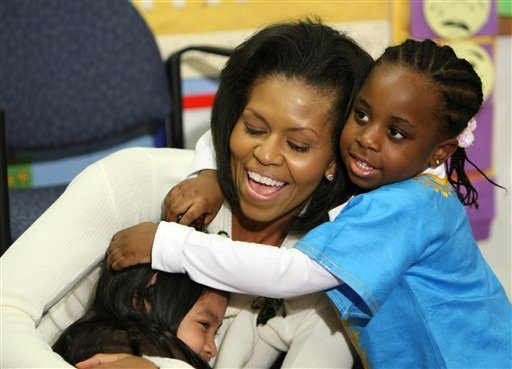 ADVANCE FOR SUNDAY, AUG. 19 AND THEREAFTER - FILE - In this Feb. 10, 2009, file photo, first lady Michelle Obama hugs children after reading a book at Mary's Center in Washington. She is 5-foot-11, and she is world-famous. Sometimes she inspires awe in her admirers. She has been accused of being the angry type. So when Michelle Obama meets people, she likes to bring things down to earth with a hug. (AP Photo/Gerald Herbert, File)