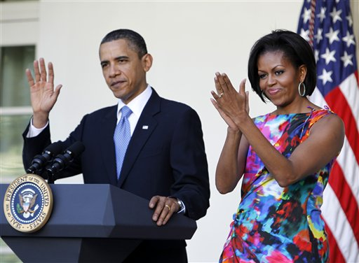 ADVANCE FOR SUNDAY, AUG. 19 AND THEREAFTER - FILE - In this May 5, 2010, file photo, President Barack Obama and first lady Michelle Obama attend a celebration of Cinco de Mayo in the Rose Garden of the White House in Washington. She is 5-foot-11, and she is world-famous. Sometimes she inspires awe in her admirers. She has been accused of being the angry type. So when Michelle Obama meets people, she likes to bring things down to earth with a hug. (AP Photo/Charles Dharapak, File)