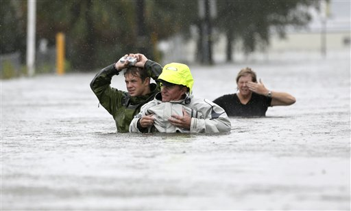 Chuck Cropp, center, his son Piers, left, and wife Liz, right, wade through floodwaters from Hurricane Isaac on Wednesday in New Orleans.