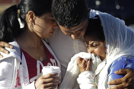 Amardeep Kaleka, son of the president of the Sikh Temple of Wisconsin, center, comforts members of the temple today in Oak Creek, Wis. Satwant Kaleka, 65, founder and president of the temple, was among four priests who died.