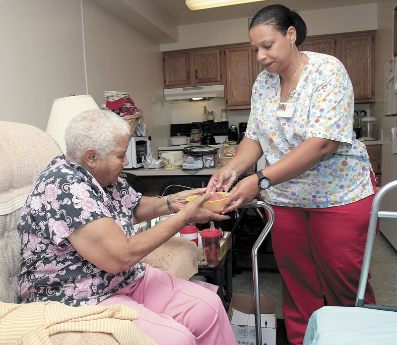 Taura Tate, right, a home care aide since 1999, hands cut watermelon to Crell Johnson, 76, on Wednesday at Johnson's apartment in Euclid, Ohio. For the past three years, she has spent four hours each weekday morning caring for Johnson, who suffered a stroke and has diabetes. Tate cooks Johnson's oatmeal for breakfast, helps her shower and makes sure she takes the right medication.