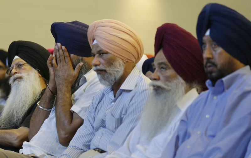 """Members of the Sikh Temple of Wisconsin react at a news conference at Oak Creek Centennial church in Oak Creek, Wis. on Monday. Officials and witnesses said a gunman walked into the temple on Sunday and opened fire as several dozen people prepared for Sunday morning services. Six were killed and three were critically wounded. Shooter Wade Michael Page played in white supremacist heavy metal bands and was a """"frustrated neo-Nazi,"""" according to the Southern Poverty Law Center."""