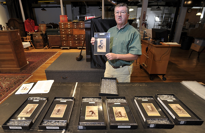 """Auctioneer Floyd Hartford discusses the value of antique 1888-89 Old Judge Cigarette cabinet cards as he holds a rare Michael """"King"""" Kelly card at the Saco River Auction in Biddeford on Friday."""