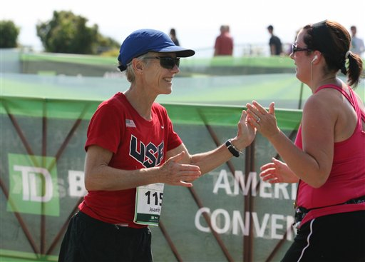 Joan Benoit Samuelson greets a runner as she crosses the finish line Saturday, Aug. 4, 2012 during the annual TD Bank Beach To Beacon 10K road race in Cape Elizabeth, Maine. (AP Photo/Joel Page)