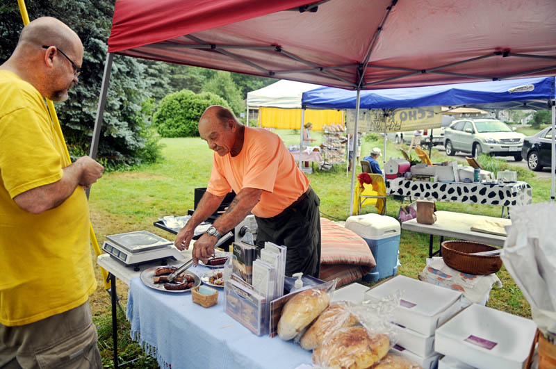 Ian Cundiff, left, samples sausage prepared by vendor Bill Trussell at the Belgrade Village Market across from the Sunset Grille on Sunday morning. Cundiff sells baked items with his wife, Julie, at the market.