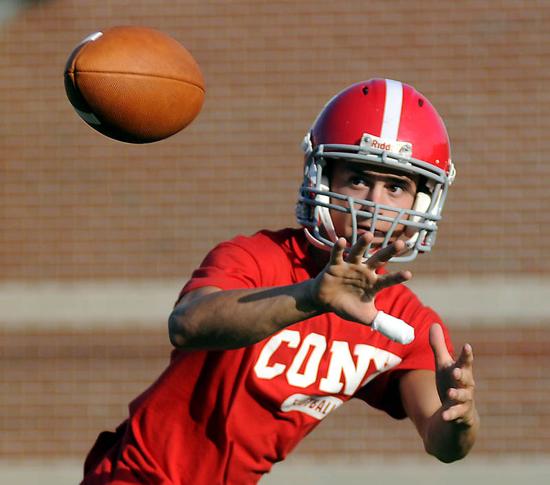 GETTING READY: Cony High School football player Chandler Shostak catches a pass Monday during the first day of practice at Cony High School in Augusta. The Rams will face Gardiner in their annual rivalry game on Friday, August 24.