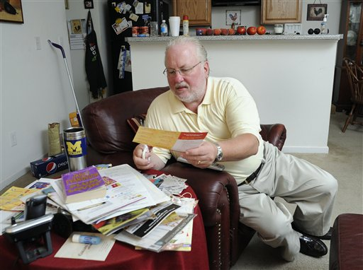 Greg Mann, an unemployed research analyst and real estate appraiser, sorts and cuts coupons at his home on Tuesday in Braselton, Ga.