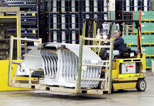 A worker at the Ford Stamping Plant moves a stack of Lincoln MKS body sides in Chicago Heights, Ill. The U.S. economy grew at a 1.7 percent annual rate in the April-June 2012 quarter, boosted by slightly stronger consumer spending and greater imports.