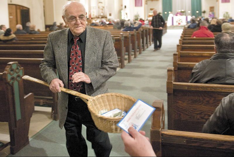 John Alves, of Dartmouth, Mass., uses a basket while taking collection during Mass on Dec. 19, 2009, at St. John the Baptist Roman Catholic Church in New Bedford, Mass. A study on the generosity of Americans, released Monday by the Chronicle of Philanthropy, found that states with populations that are less religious are also the stingiest about giving money to charity.
