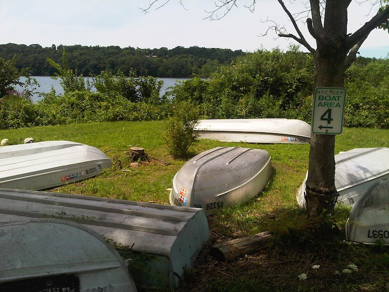 Rowboats sit on the shore of Lake Gleneida in Carmel, New York, Tuesday Aug. 7, 2012, where a woman drowned, and and a 6-year-old clinging to the floating corpse was rescued by three people fishing in a rowboat. Authorities said an autopsy was planned to determine if the woman drowned or suffered some kind of medical emergency while wading with the girl in the water. (AP Photo/Jim Fitzgerald)