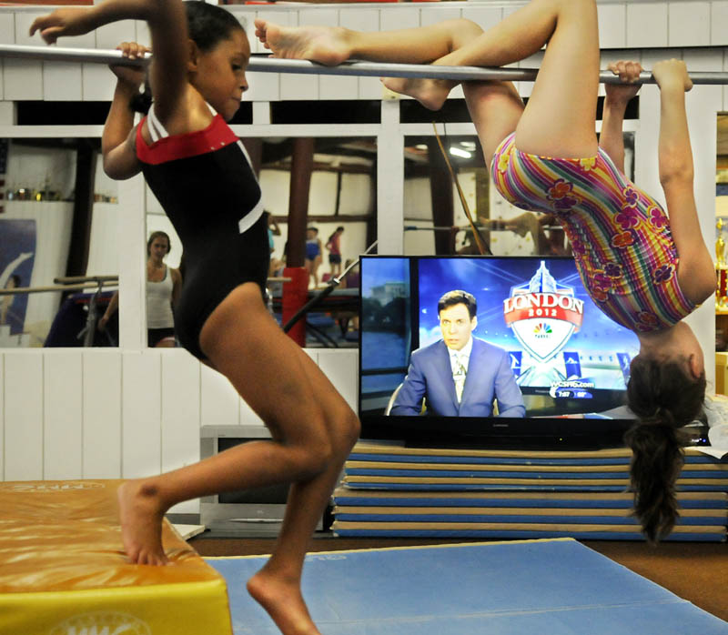 RAISING THE BAR: Girls with Decal Gymnastics train Tuesday on the bars at Mainely Gymnastics in Augusta while watching the Olympics. The gymnasts had a party to celebrate the games.
