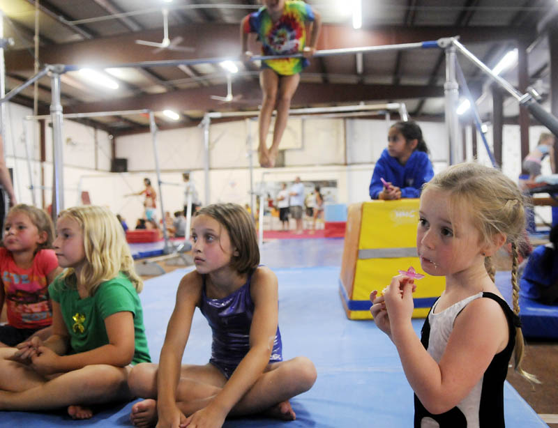 STAFF PHOTO BY ANDY MOLLOY RAISING THE BAR: Cariana Rollins eats a cupcake Tuesday at Mainely Gymnastics in Augusta while watching the Olympics. Gymnasts had a party at the gym to celebrate the games.