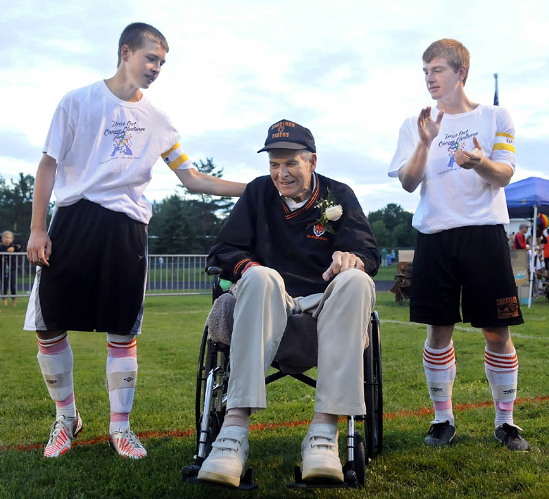 TIGER CAPTAIN: Gardiner Area High School captains Keegan Smith, left, and Daniel Del Gallo, right, introduce their honorary captain, Arthur Warren, before the boys soccer game Monday against Cony High School before the Drive Out Cancer Challenge game held in Gardiner.