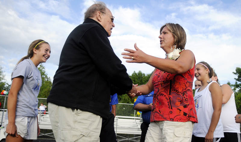 GOOD LUCK: Cony High School girls soccer team honorary captain Bill Ottman, left, and Gardiner Area High School honorary captain Nancy Hicks great each other Monday before the coin toss before the Drive Out Cancer Challenge game to raise funds for cancer research in Gardiner.