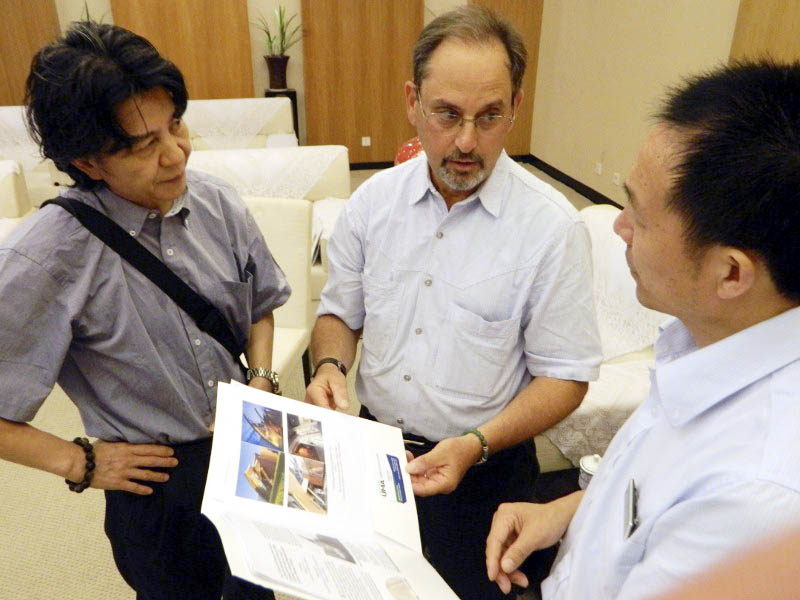 University of Maine at Augusta Professor Robert Katz, center, with interpreter, left, and, the vice director of the Memorial Hall of the Victims in Nanjing Massacre by Japanese Invaders present educational materials developed by the Holocaust and Human Rights Center of Maine.