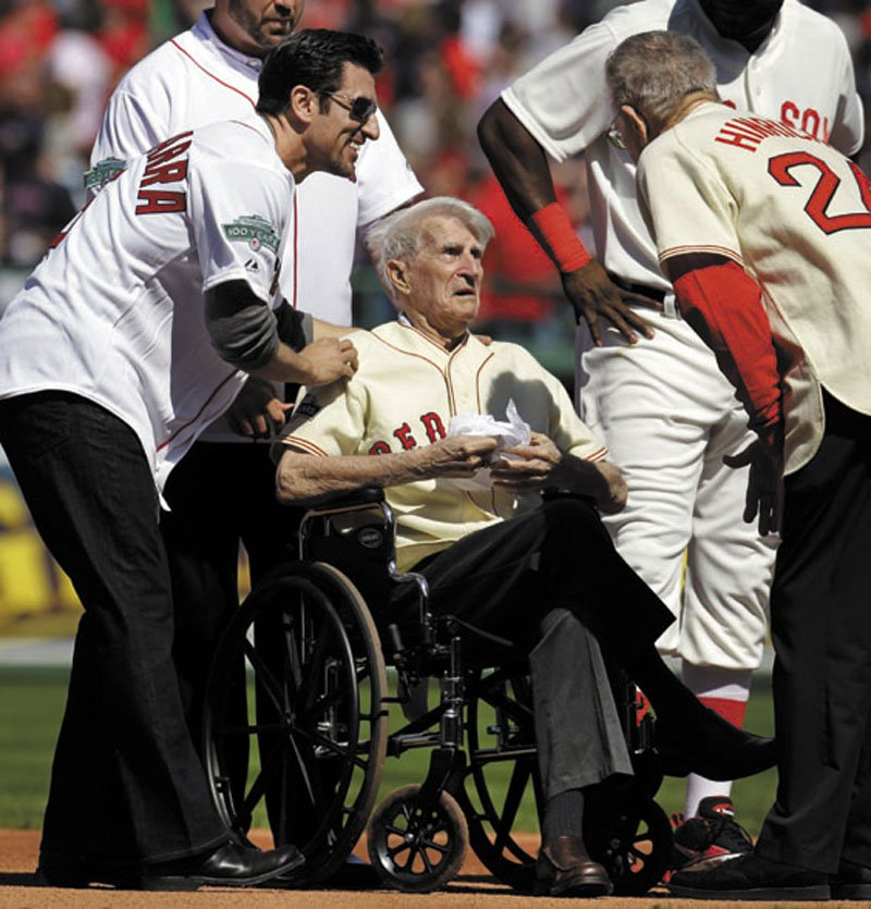 Boston Red Sox great Johnny Pesky, center, is greeted in April by former player Nomar Garciaparra, left, and others during a celebration of the 100th anniversary of the first regular-season baseball game at Fenway Park prior to the Red Sox taking on the New York Yankees in Boston. Pesky, who spent most of his 60-plus years in pro baseball with the Red Sox and was beloved by the team's fans, died on Monday, in Danvers, Mass. He was 92.