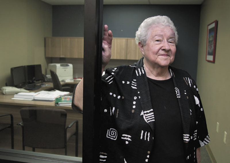 """Janice Durflinger poses for a photo at her workplace last week in Lincoln, Neb. Durflinger is still working at age 76, running computer software programs for a bank. Still, she worries that a higher retirement age would be tough on people with more physically demanding jobs. """"No matter how much you exercise, age takes its toll,"""" Durflinger said."""