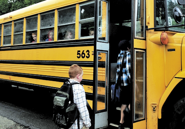 Staff photo by David Leaming FIRST STEP: As other kids watch from inside the school bus Jordan Pomeroy follows his brother Ben into the bus in front of their home in Burnham on the first day of school for School Administrative District 53.
