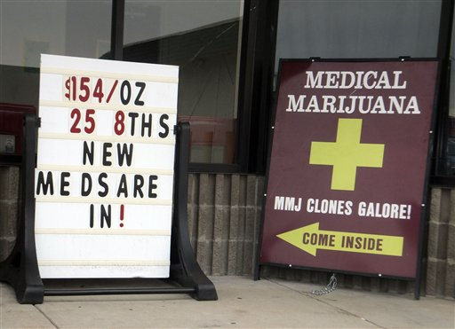 """Sidewalk ads outside a west Denver medical marijuana dispensary advertise low prices and """"Clones Galore!"""" on Monday."""
