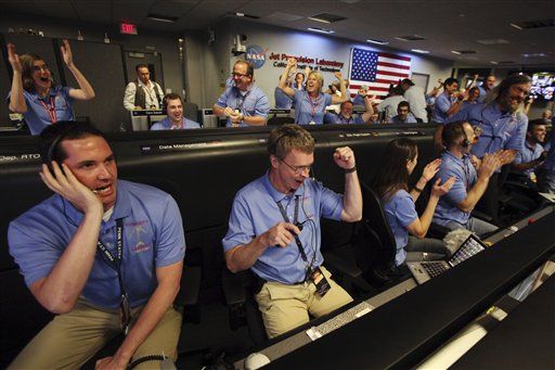 Peter Ilott, center, and his colleagues celebrate a successful landing inside the Spaceflight Operations Facility for NASA's Mars Science Laboratory Curiosity rover at Jet Propulsion Laboratory in Pasadena, Calif. on Sunday. The Associated Press photo
